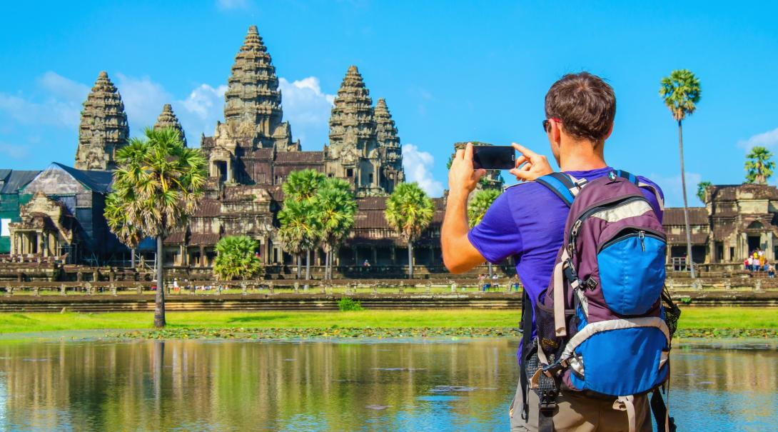 Traveller takes a photo of Angkor Wat during his travels through Cambodia.